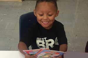 Pre-K student holding books received from Barb's Books Initiative