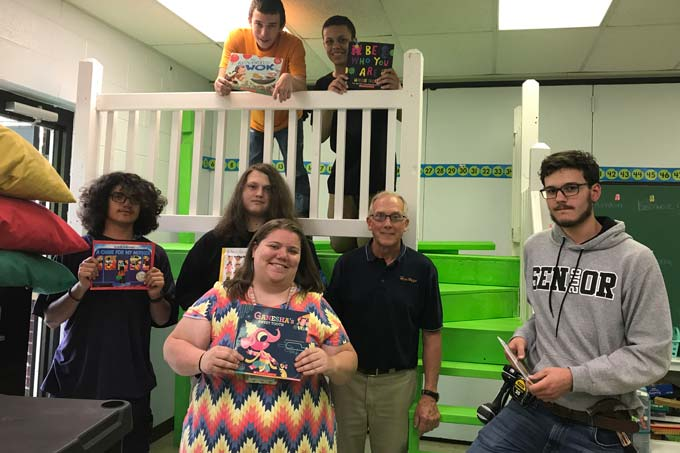 Heritage CTE students standing with books around reading loft