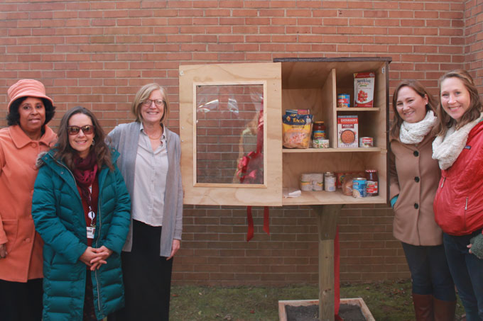 Staff and volunteers standing next to Little Free Pantry at Hutcherson