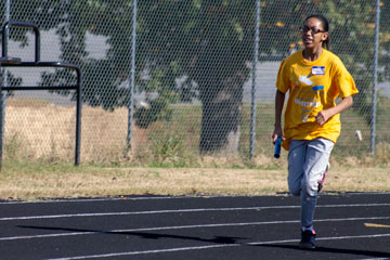 Student running with baton on track