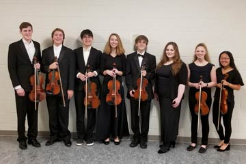 Eight orchestra students together in performance attire