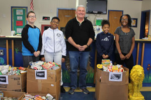 "LES students standing with ""souper bowl"" canned food drive items"