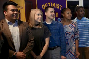 Students standing in front of Optimist Club banner