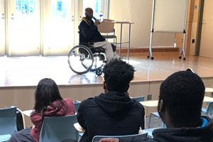 Man in wheelchair on stage speaking to students