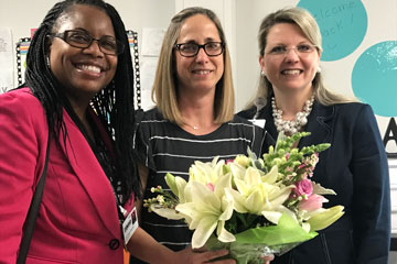 2018 Teacher of the Year holding flowers with superintendent and principal