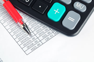 Calculator and pen sitting on print out of spreadsheet