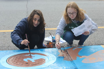 Two students painting storm drain