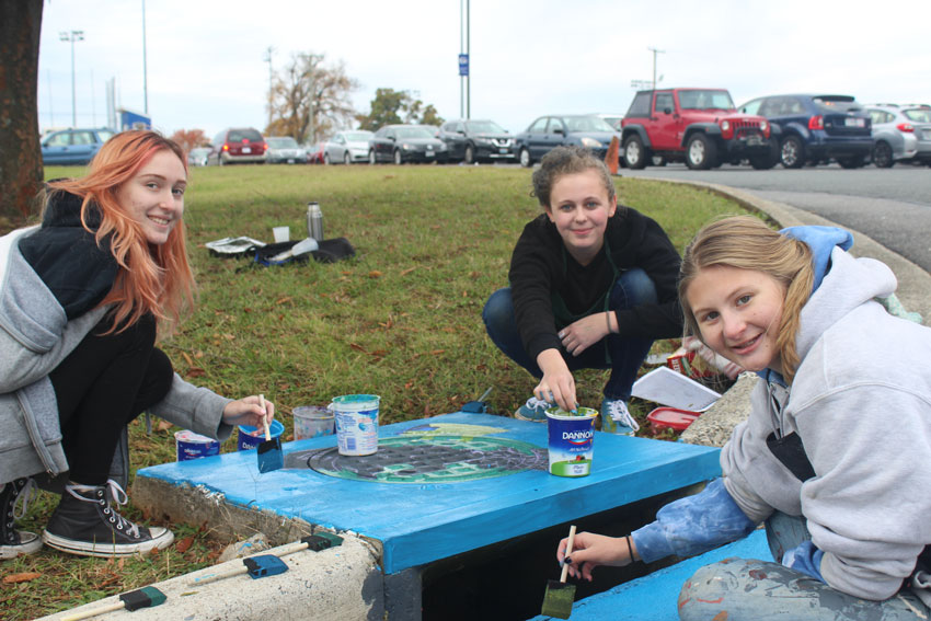 Three students painting storm drain