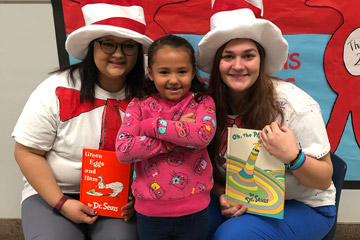Two women holding books while wearing hats posing with elementary student