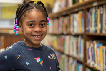 Elementary age girl smiling in school library