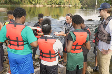 Students in life vests standing by the James River