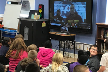Students in classroom video chat with NFL players