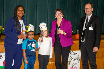 Administrators and students pose with Virginia Secretary of Agriculture Betina Ring while holding glasses of milk