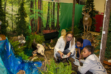Teacher and students in classroom with woodland decorations