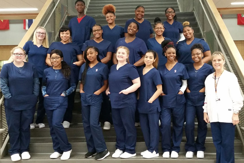 Nurse aide students wearing scrubs standing on steps