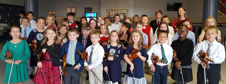 Large group of strings students standing with violins