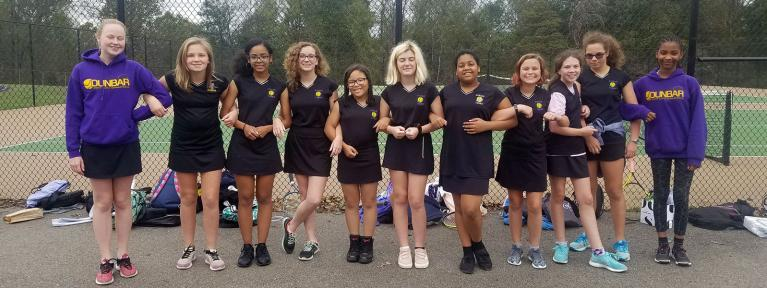 Girls tennis team posing together locking arms