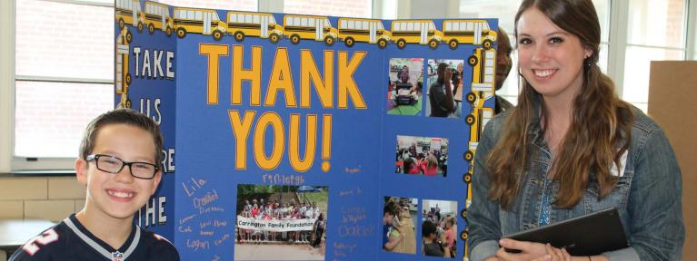 "Teacher and student standing in front of display board that reads ""Thank You"""