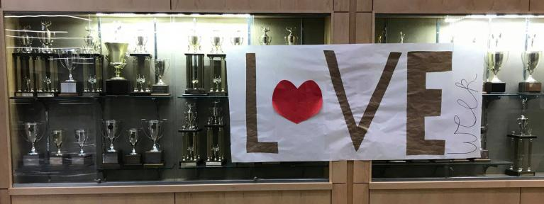 trophy case with love week banner