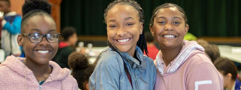 Three girls smiling in cafeteria