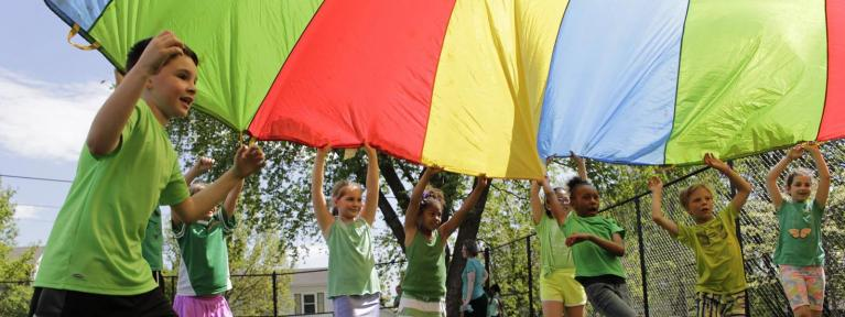 Students playing with rainbow color parachute