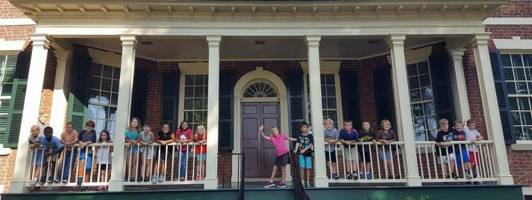 Students standing on porch of historic house