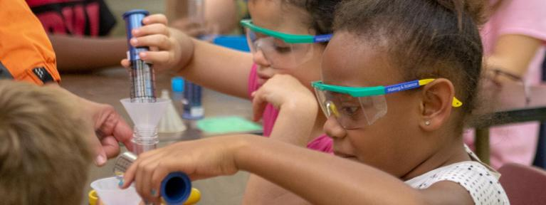 Students wearing goggles pouring liquid in test tubes
