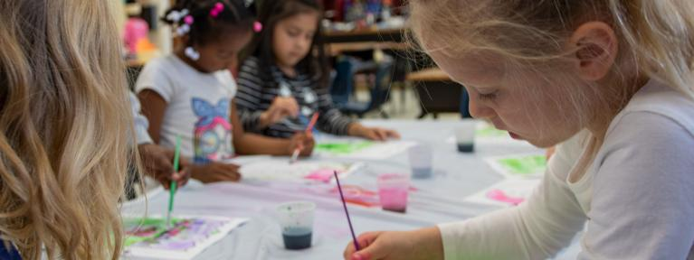 Elementary students painting at a table