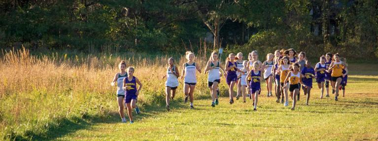 Girls cross country athletes running course